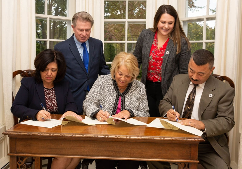 President Virginia Horvath, flanked by Fredonia Mayor Athanasia Landis, Dunkirk Mayor Willie Rosas, sign documents that formalize the Central Connection MOU