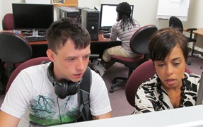 Ms. Skemer helps Patrick with his financial aid in our computer lab.