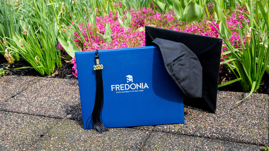 photo of diploma cover and mortarboard