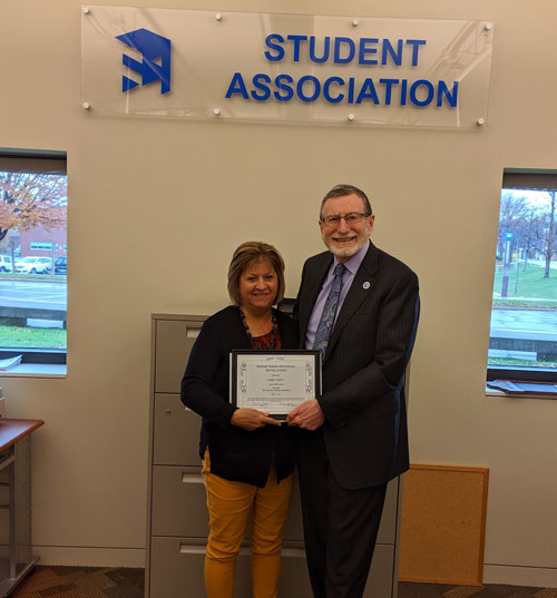 Interim President Dennis Hefner presents the Barbara Saletta Meritorious Service Award to Kathy Carrus in the SA office.