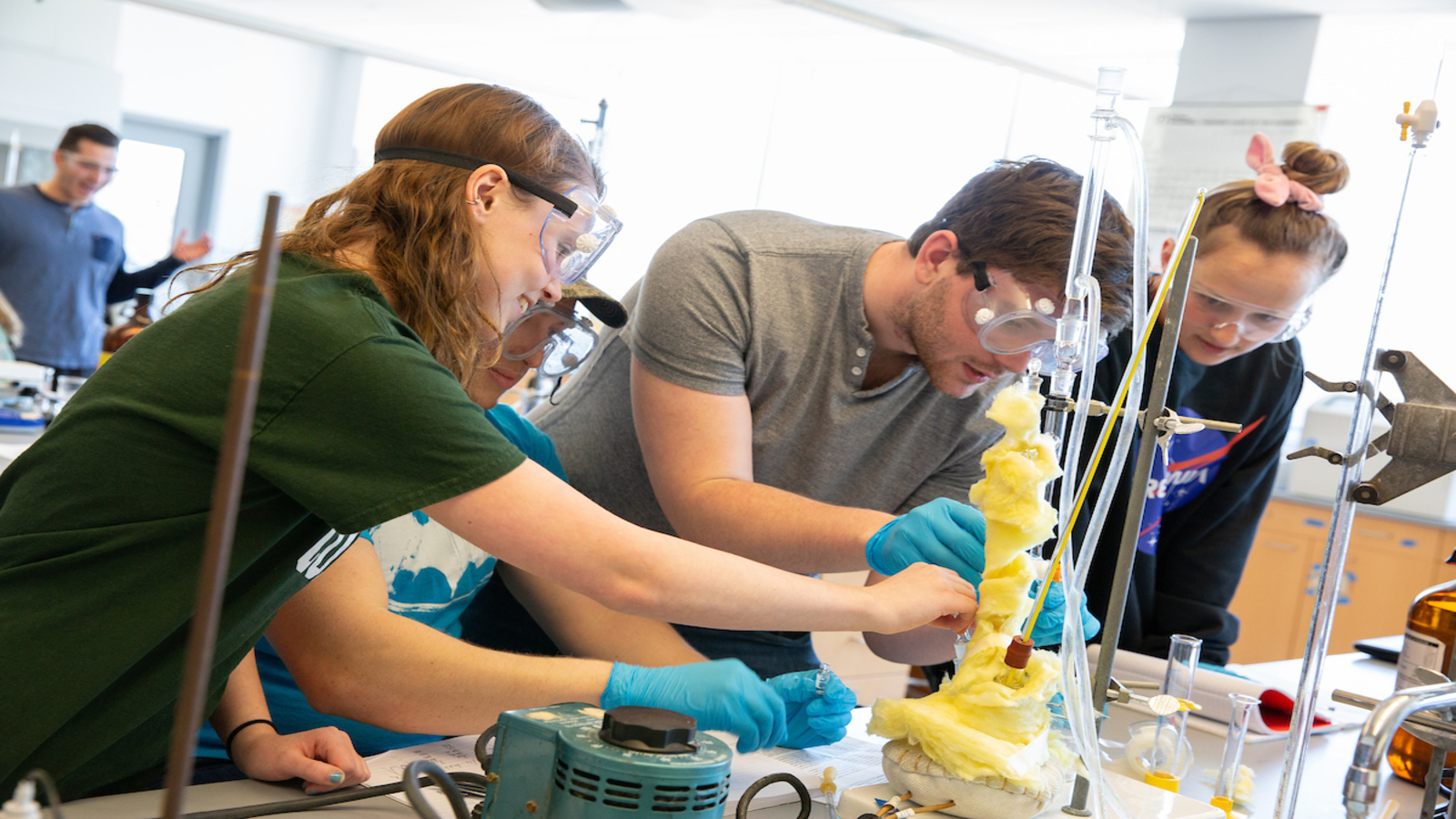 Fredonia students work together on an experiment in a lab