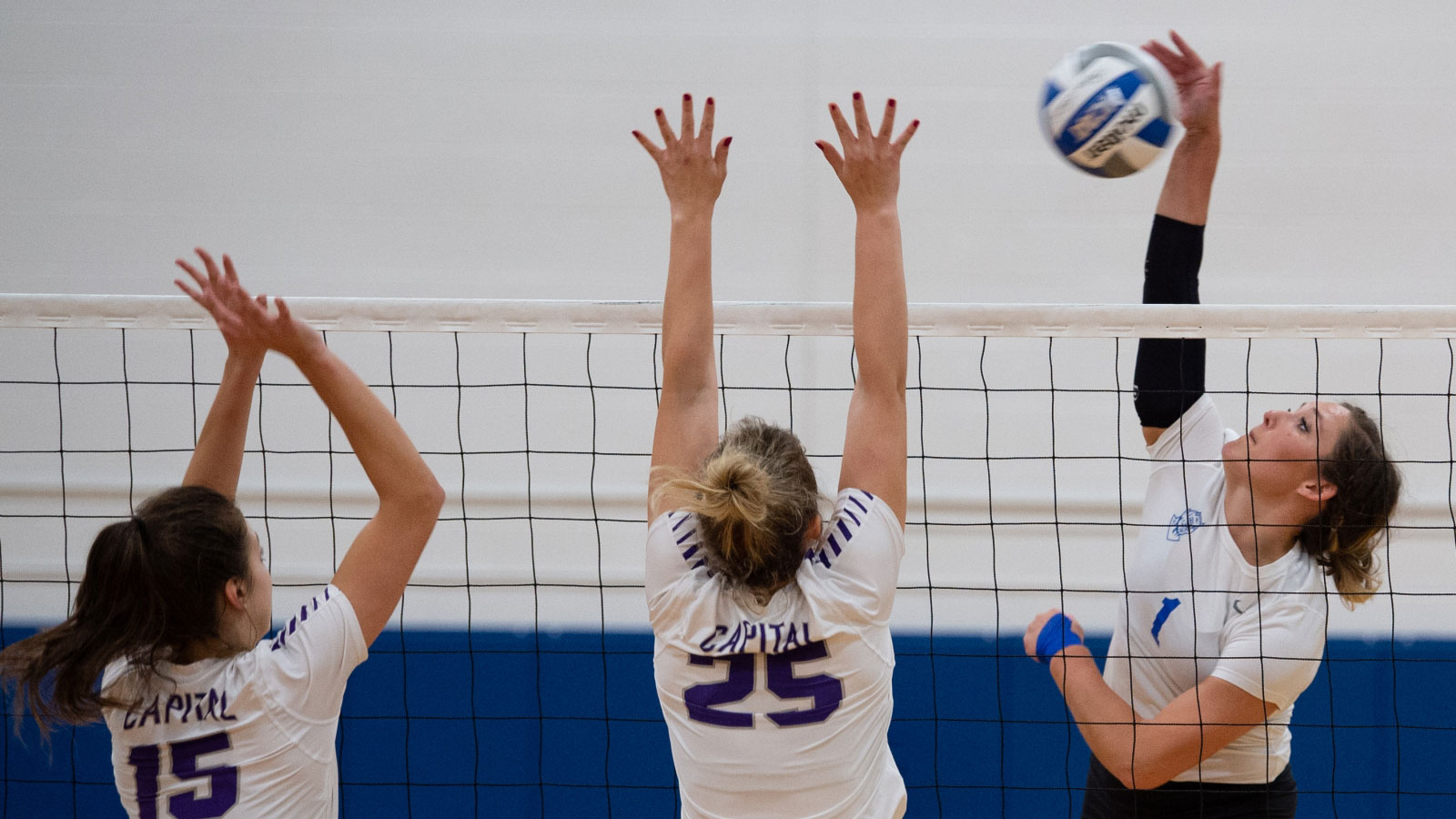 a close up of a womens volleyball player hitting the ball over the net during a match