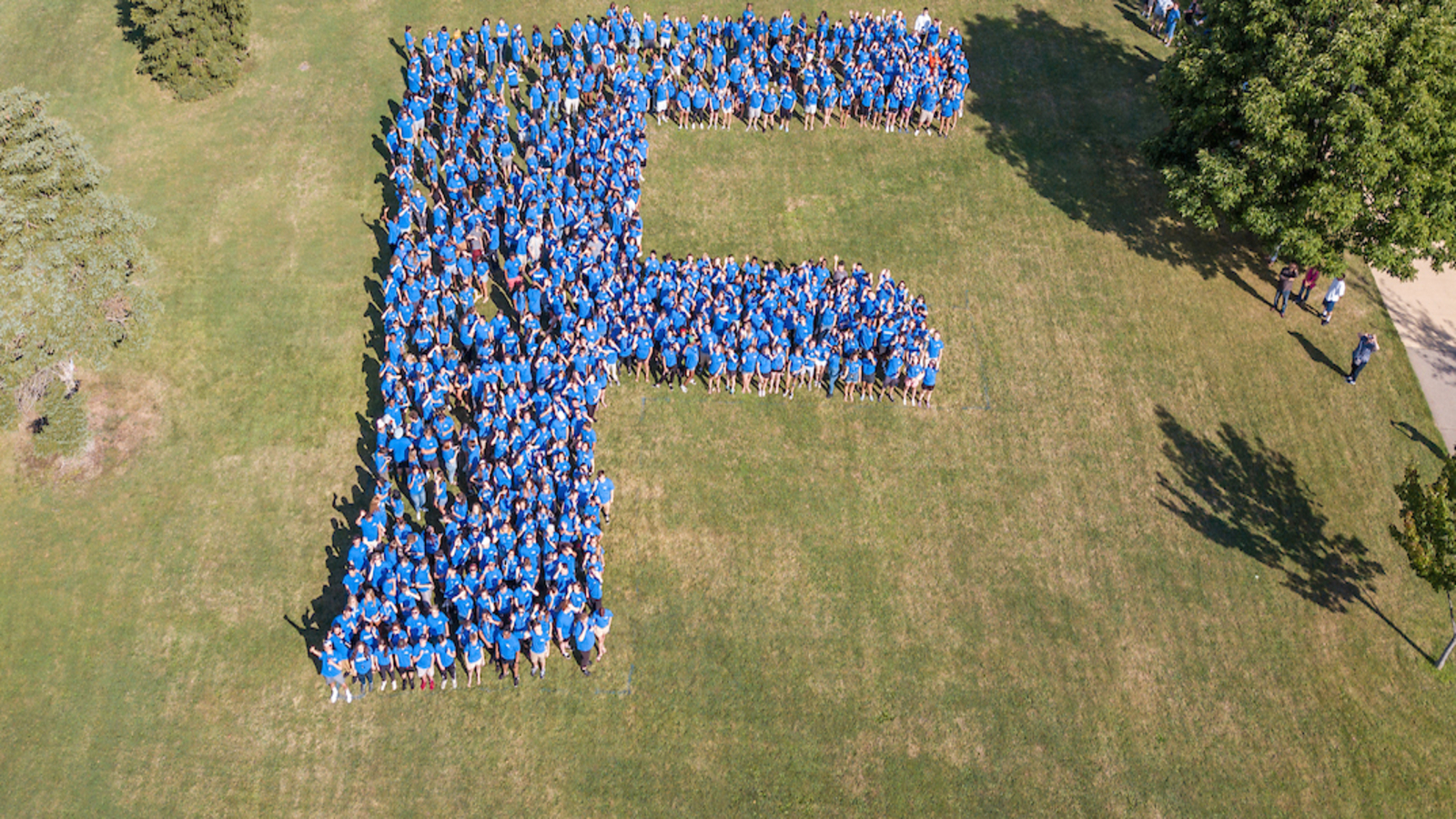 "aerial photo of students forming the Fredonia ""F"" on the lawn"