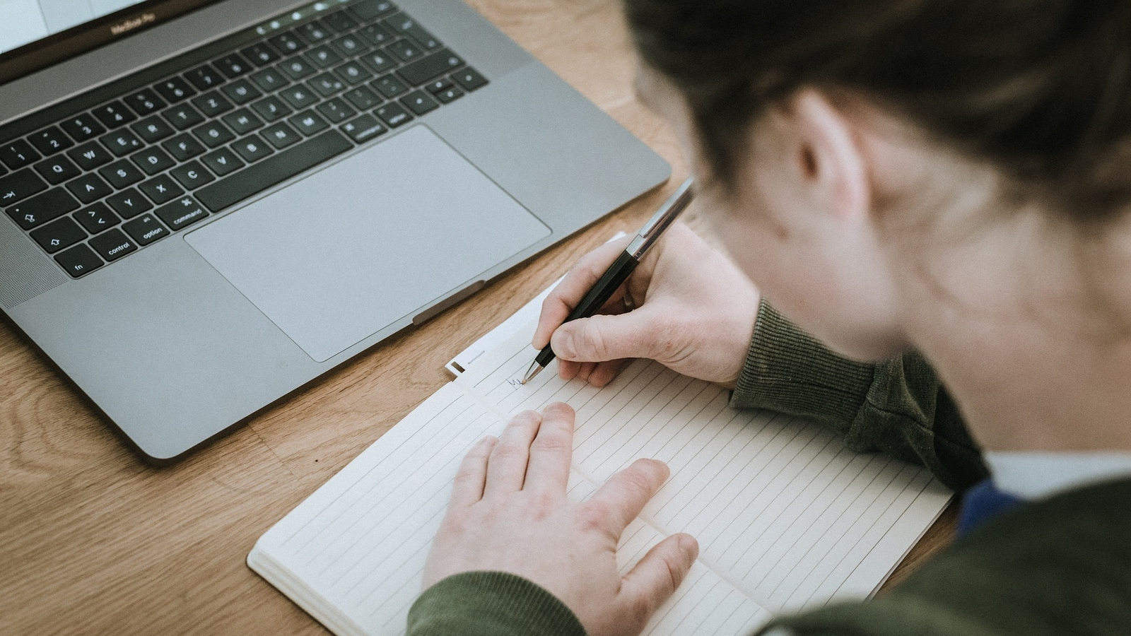 person writing in notebook with laptop open