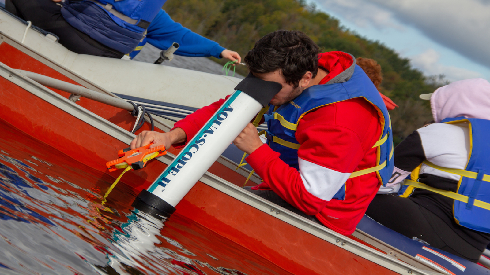 a biology student looks through a large microscope to examine underwater elements while in a canoe