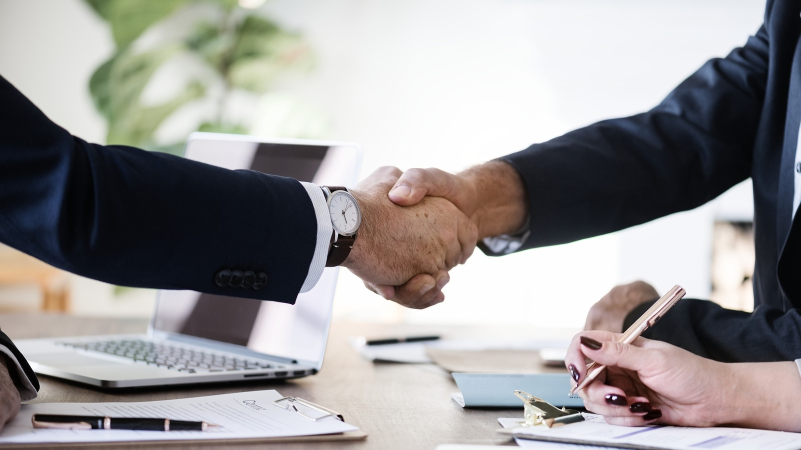 Two people engaged in a business deal shake hands across a table