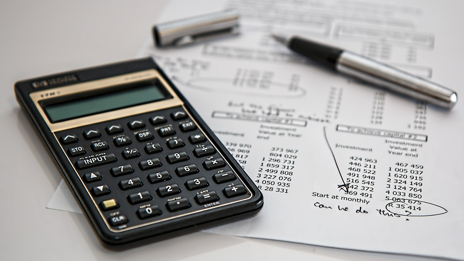 A photo of a calculator sitting on top of paper indicating a financial spreadsheet