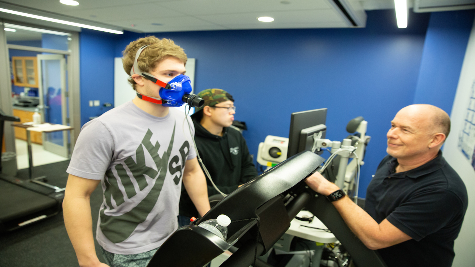 a student walks on a treadmill while wearing gear monitoring his breathing