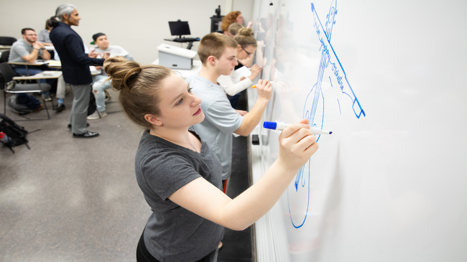 students drawing logos on a whiteboard in the front of a classroom
