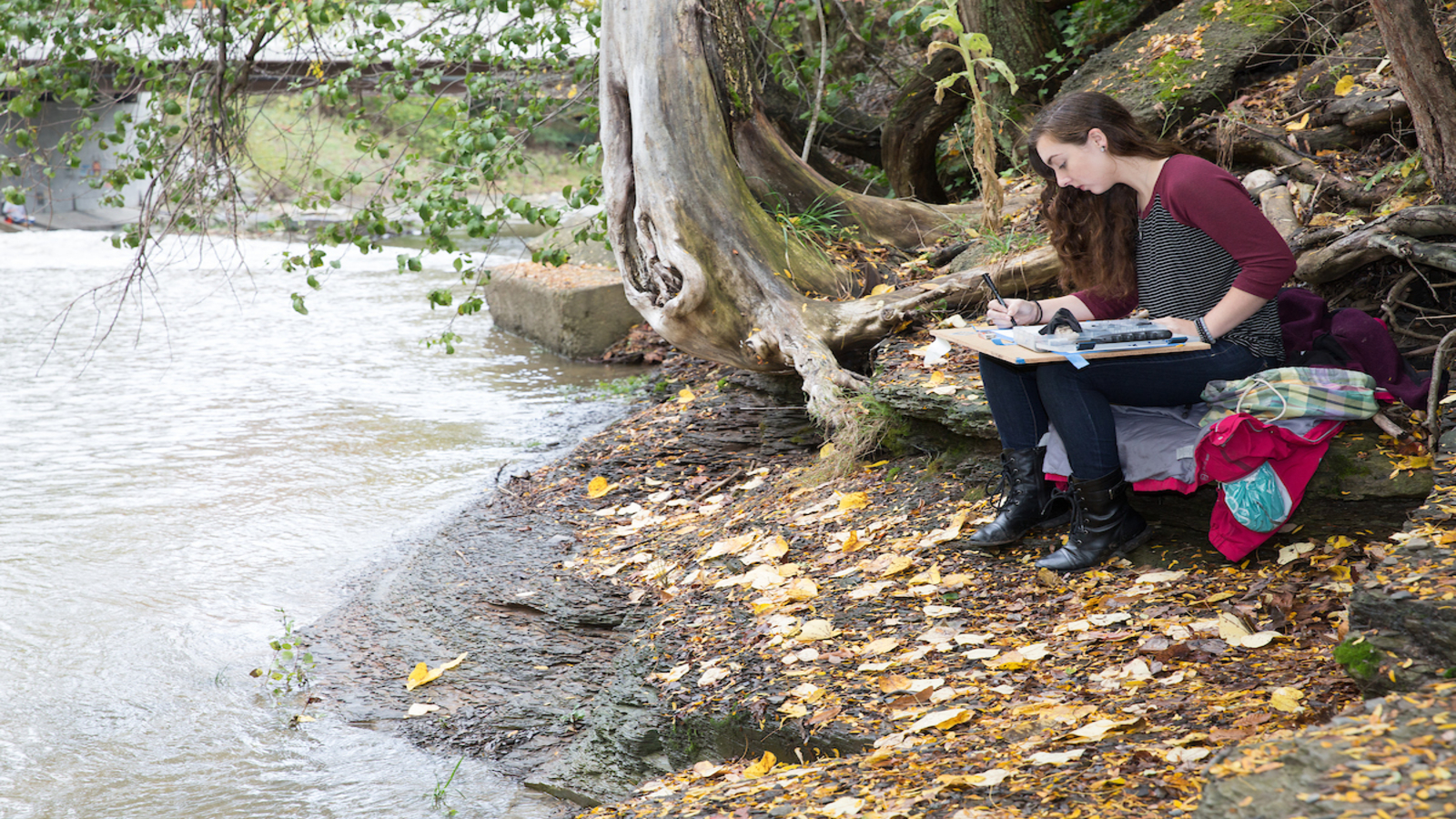 a student paints along the edge of local creek