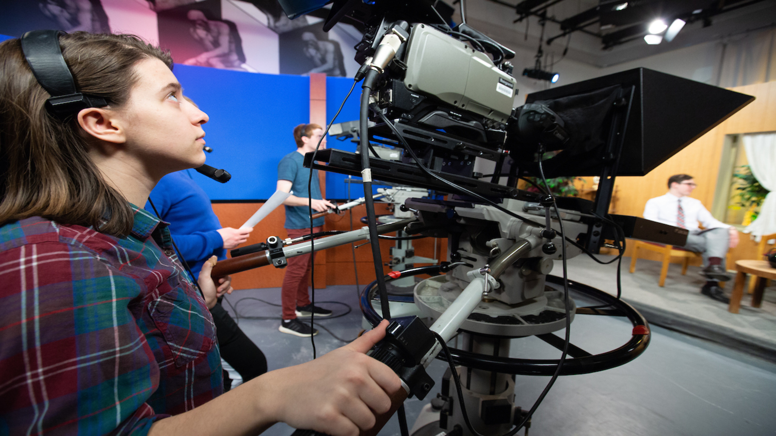 a student operates a camera for a television production in the Thompson TV studio