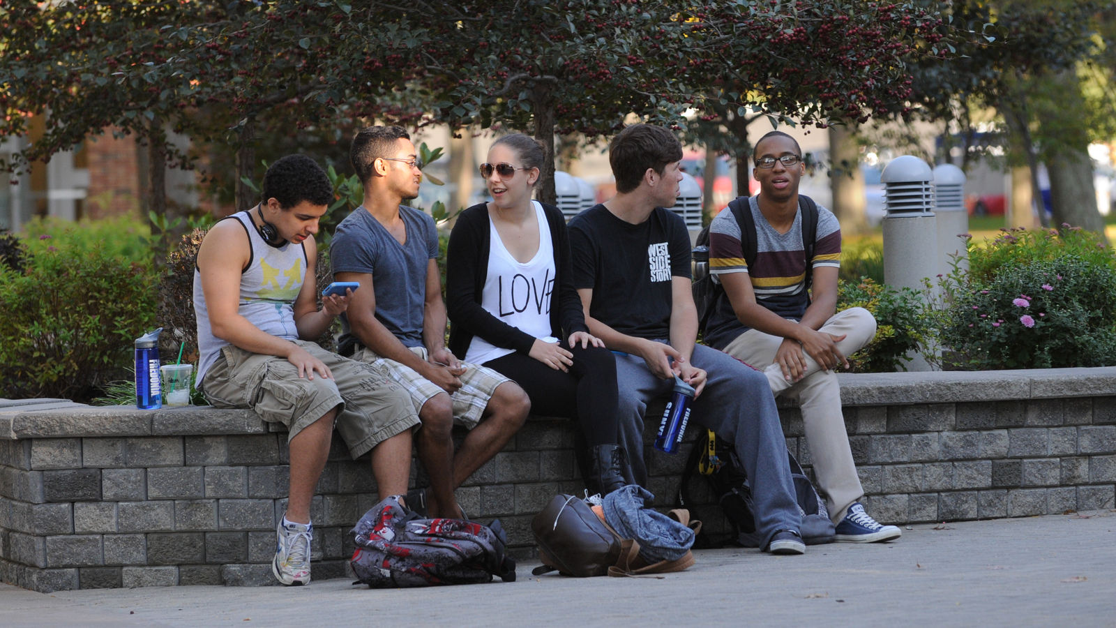 Students sitting over a bench