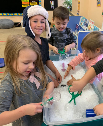 Children having fun exploring their five senses and playing at the sensory table.