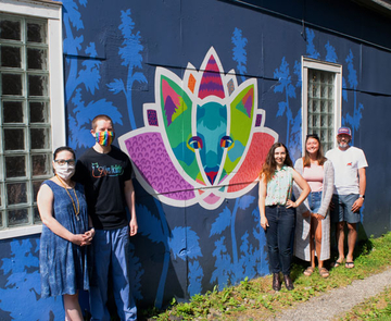 students and faculty in front of mural