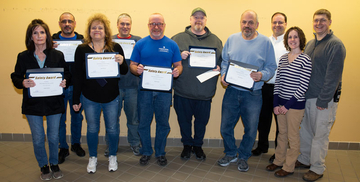 Staff displaying their Custodial Safety Incentive Award certificates