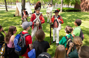 Students gather around a British encampment from the American Revolutionary War at last year's Living History Day at Fredonia.