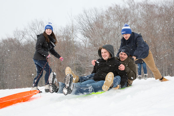 students sledding in the snow