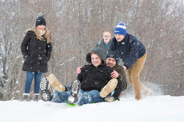 students snow sledding