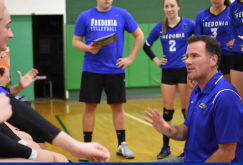women's volleyball coach Geoff Braun instructs his players during a match