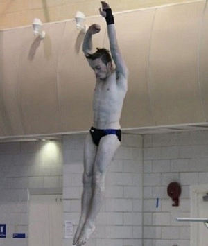 a diver is in mid-air as he jump on the board to begin his dive