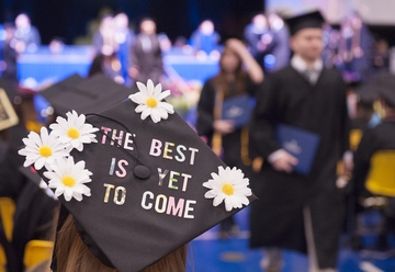 "a photo of a mortarboard from commencement that reads ""the best is yet to come"""