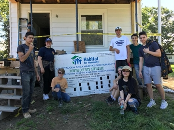habitat for humanity students pose on the front porch of a home they are working on