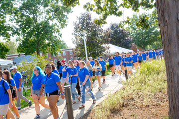 large group of students wearing blue walk down a sidewalk
