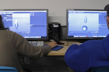 students look a a computer screen working on an animation project