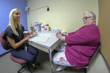 a fredonia student works with a community member in a clinic room