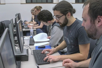 3 students examine a computer screen in the computer lab in Fenton Hall