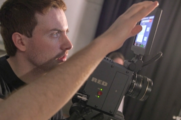 a fredonia student operates a camera in the tv production studio