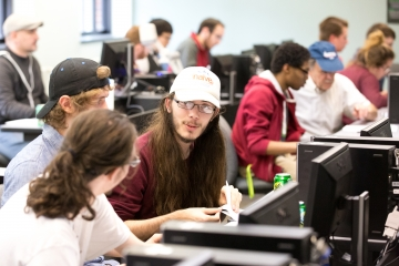 3 students talk while participating in a computer science competition