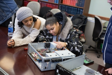 2 students work on a computer rebuilding project