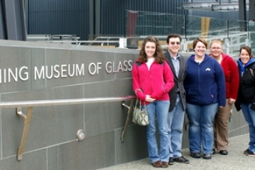students pose for a photo at the entrance to Corning Museum of Glass