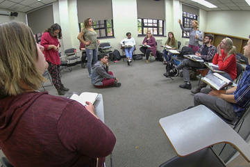 Students in Dr. Ann Seigle Drege's English class sit in a  circle and discuss Shakespeare