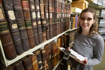photo of student Rebekah Denz next to a stack of library books