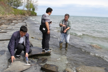 geology students examine rocks along a local beach