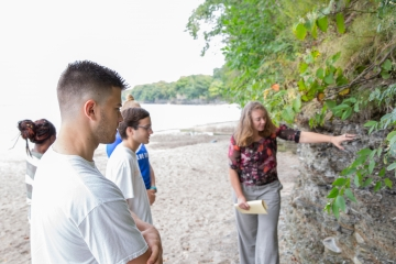 a geology professor examines a rock formation with geology students along a beach