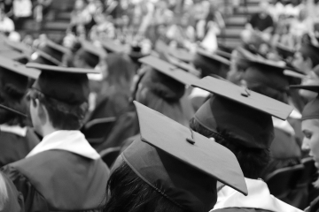 black and white image of graduation caps during a commencement ceremony