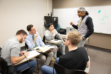 a professor engages with three students at their desk in a classroom