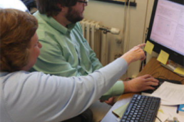 a fredonia professor points to a computer while advising a student