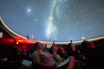 students look at the stars in the planetarium