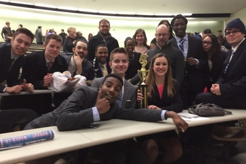 the mock trial team poses with a trophy after winning a competition