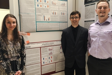 psychology students pose in front of the research presentation posters