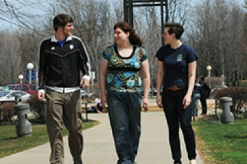 3 students walk across campus