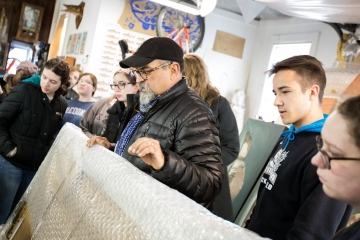 students examine artwork in a studio