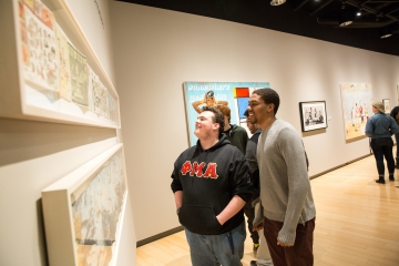 students look at art pieces during a gallery opening
