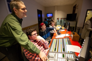 a professor assists a student operating the television switcher in the tv studio