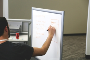 a man writes notes on a whiteboard