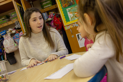 Graduate education students works with students in a local classroom